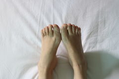 Foot on white bed royalty free stock images