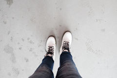 Foot of woman with blue jean pants standing in cement floor Royalty Free Stock Image