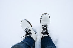 Foot of woman with blue jean pants standing in snow Stock Images