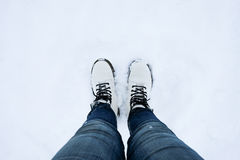 Foot of woman with blue jean pants standing in snow Royalty Free Stock Image
