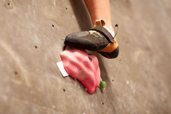 Foot of woman on indoor climbing gym wall hold. Fitness, extreme sport, bouldering, people and equipment concept - foot of young woman in rock shoe on indoor stock photo