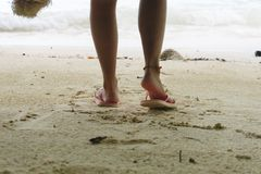 Foot of woman wearing pink sandal standing on sand beach are bac. Foot of young woman wearing pink sandal standing on sand beach are background. this image for Stock Photography