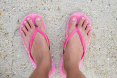 Foot of woman wearing pink sandal standing on sand beach are bac Royalty Free Stock Image