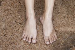 Foot of women on water. Set foot on the sand with water of small river Stock Image