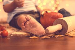 The foot of a young child in the kitchen. The concept of baby food, care for children and their nutrition. Helping a child mom