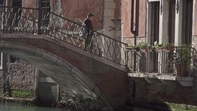 Bridge spanning a small canal in Venice and people crossing stock footage