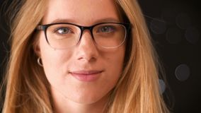 Footage blonde caucasian female in glasses is moving to camera from blurred dark background, casual style and close-up stock video footage
