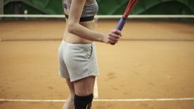 Footage from the bottom up of a sports, long haired woman with a physical disability playing tennis. Close up.  stock video