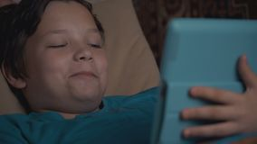 Footage boy using tablet pc lying on sofa. stock footage