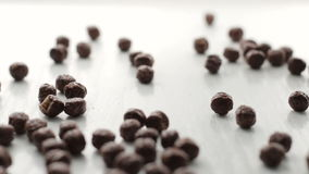 Footage from brown round cocoa cacao flakes falling on white wooden table with soft focus stock video