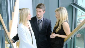 Footage of businessman and two businesswomen speaking on stairs Stock Photography