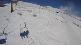 Footage chairlift with skiers moving to the top of the mountain in a wonderful sunny day. Tonale, Ponte di Legno, Italy. Footage chairlift with skiers moving to stock video