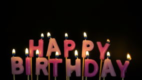 Footage colorful burning candles set on black background. Happy Birthday candles. stock video footage