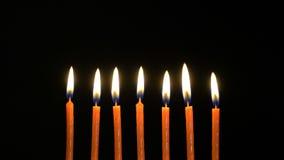 Footage colorful burning candles set on black background. 4k stock footage