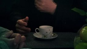 A cup of tea and a man`s hand. This is footage of a cup of tea and a man`s hand sitting in a cafe stock footage