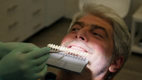Footage of a dentist checking a young mans shade of tooth color stock video