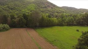 Descent towards the meadow in the distance of a beautiful forest and hill. This is a footage of Descent towards the meadow in the distance of a beautiful forest stock footage