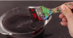 Footage of dirty paint brush being cleaned