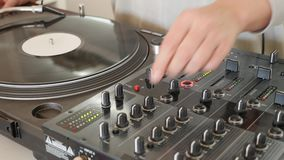 Footage of a DJ scratching on a vinyl and mixing music on an audio mixer.  stock video footage