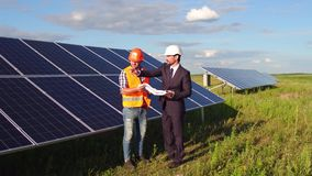 On footage foreman and business client meeting in the field at solar energy station. Men standing close to solar panels, looking at engineering drawings stock footage