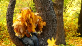 Footage girl sitting on a tree and holding autumn leaves. HD video. slow motion 120fps stock video