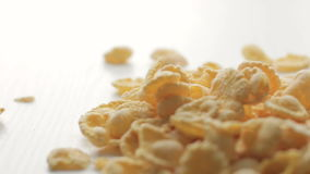 Footage from golden cornflakes falling on white table with soft focus on middle ground stock video