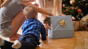 4k footage of happy family taking cat out of Christmas gift box. Pet as gift for New Year. Footage of happy family taking cat out of Christmas gift box. Pet as stock footage
