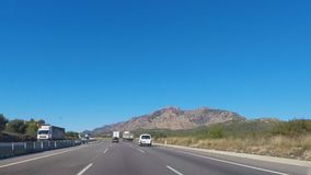 Driving On The Hiwhay Overtaking Trucks. This is footage of a highway with several lanes, and separated lanes as well. The cars drive by as this is filmed from stock footage
