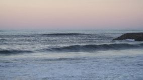 Footage of incoming waves rolling towards the sand beach during a foggy sunset. Close up footage of incoming waves rolling towards the sand beach during a foggy stock footage