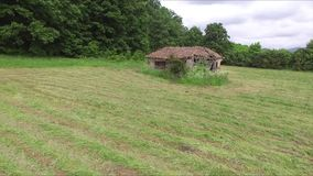 Low aerial towards abandoned house in the meadow. This is footage of low aerial towards abandoned house in the meadow stock footage