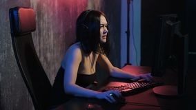 Girl gamer in headphones and with mouse and keyboard in her hands playing network games preparing to participate in