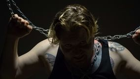 Frightened blond captive bound in chains. Footage of a man bound in chains in studio stock video