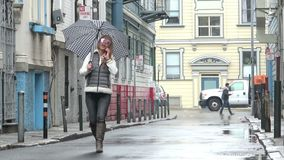 Rain. Woman walking down a city street talking on her cell phone stock video