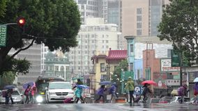 Rainy Weather. School Children with rain gear is rushing across a busy city street. stock footage