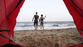 Footage from the red tent near the sea. Smiling, happy young woman in denim shorts asking to join her boyfriend to the. Sea stock video footage