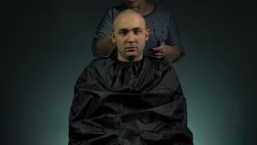 Hairstylist shaving a brunette man. Footage of shaving man`s head on grey background stock video