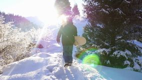 Footage of snowboarder man adventure, walking to snowy alps mountains stock footage