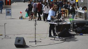 Street Music At University Campus. This is footage of of a street musician playing music on the street in an university campus stock footage