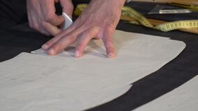 Footage of a tailor drawing final lines on fabric before he cuts it into parts for further process