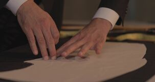 Footage of a tailor drawing lines on fabric and making some alterations around the cut with his chalk-flat profile