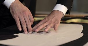 Footage of a tailor drawing lines on fabric and making some alterations around the cut with his chalk
