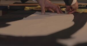 Footage of a tailor drawing lines on fabric and making some alterations arround the cut with his chalk-flat profile