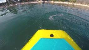Back of SUP board. Footage taken from back of stand up paddling board moving forward while person paddling stock video footage