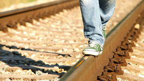 Footage turns colorful from black and white: a person walks along railway wearing sneakers stock video