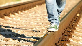A footage turns colorful while a teenager walks along the rail wearing sneakers stock footage