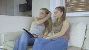 Footage of two girls at home sitting on sofa using a tablet and smiling. Two beautiful young women at home sitting on sofa  using a tablet PC computer and stock footage