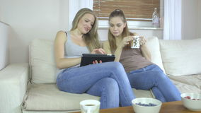 Footage of two girls at home sitting on sofa using a tablet and smiling. Two beautiful young women at home sitting on sofa  using a tablet PC computer and stock video footage
