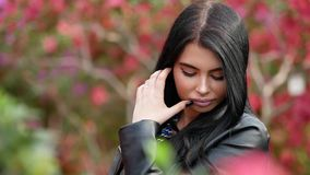 Footage of young attractive woman in black leather jacket posing over green exotic background with flowers. 4K footage of young attractive woman in black leather stock video footage