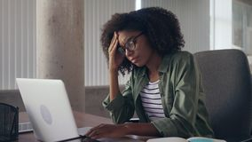 Stressful young businesswoman at desk using laptop stock footage