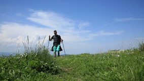 Man hiking in mountains. Footage of a young man with nordic sticks hiking in mountains stock video footage